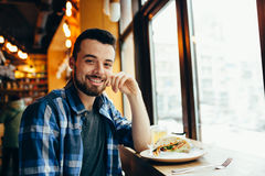 Young man having lunch at cafe. Attractive guy is sitting near the window and holding up his chin. He is smiling stock image