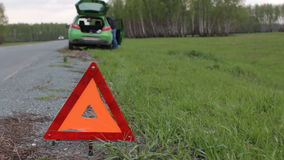 Young man having problem with car, red triangle on the rural road stock video footage