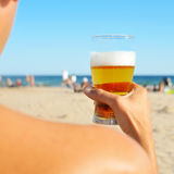 Young man having a refreshing beer on the beach Royalty Free Stock Images
