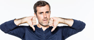 Young man having regrets,expressing disappointment,sadness with thumbs down. Annoyed handsome young bearded man having regrets, expressing his disappointment Royalty Free Stock Images