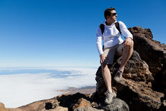 Young Man Having a Rest in a High Peak Over Clouds Stock Image