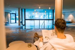 Young man having a rest in the SPA by the open pool in a robe. Reading magazine. royalty free stock photos