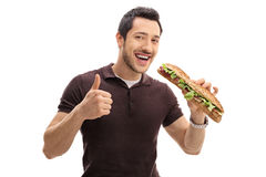 Young man having sandwich and making thumb up gesture Royalty Free Stock Photo