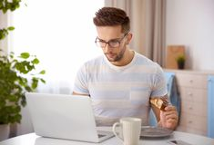 Young man having snack while working with laptop. In kitchen Stock Photo