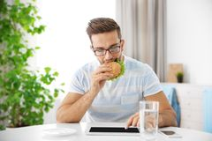 Young man having snack while working with tablet computer. In kitchen Stock Image