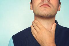 Young man having sore throat and touching his neck, wearing a loose t-shirt against light blue background. Hard to swallow. nodule stock images
