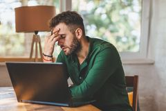 Young man having stressful time working. On laptop royalty free stock photos