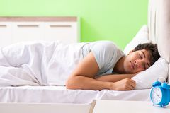 The young man having trouble waking up in early morning. Young man having trouble waking up in early morning stock photos