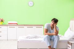 The young man having trouble waking up in early morning. Young man having trouble waking up in early morning royalty free stock images