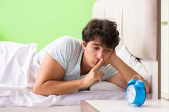 The young man having trouble waking up in early morning. Young man having trouble waking up in early morning royalty free stock photo