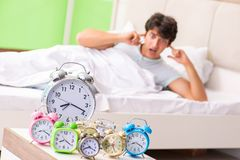 The young man having trouble waking up in early morning. Young man having trouble waking up in early morning stock photo