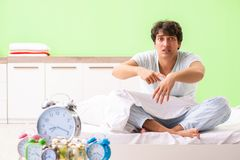 The young man having trouble waking up in early morning. Young man having trouble waking up in early morning stock images