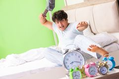 The young man having trouble waking up in early morning. Young man having trouble waking up in early morning royalty free stock photography