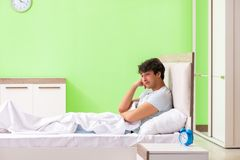 The young man having trouble waking up in early morning. Young man having trouble waking up in early morning royalty free stock photos