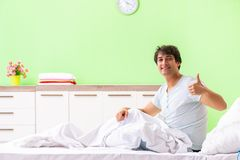 The young man having trouble waking up in early morning. Young man having trouble waking up in early morning royalty free stock image