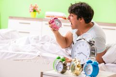 The young man having trouble waking up in early morning. Young man having trouble waking up in early morning stock photography