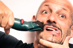 Young man having Troubles with electric Shaver Stock Photo