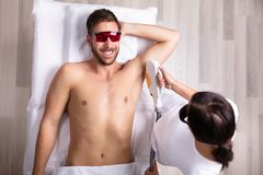 Young Man Having Underarm Laser Hair Removal Treatment. Close-up Of Smiling Young Man Having Underarm Laser Hair Removal Treatment In Spa stock images