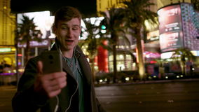 Young man is having a video chat on a street at night. Young cheerful guy is doing a video translation over his smartphone while standing on a street of Las stock footage