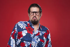 Young man in Hawaiian shirt making a face against red background Royalty Free Stock Photos
