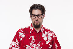 Young man in Hawaiian shirt making a face against white Royalty Free Stock Photos