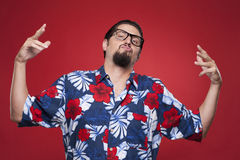 Young man in Hawaiian shirt posing against red background Stock Photo