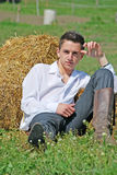 Young man on hay bale Stock Images