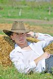 Young man on hay bale Stock Photography