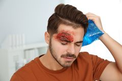 Young man with head injury in clinic. First aid stock images