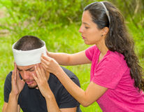 Young man with head injury receiving treatment and bandage around skull from woman, outdoors environment Stock Photos