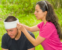 Young man with head injury receiving treatment and bandage around skull from woman, outdoors environment Royalty Free Stock Images