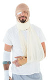 Young man with head tied up in bandage and broken hand Stock Photography