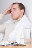 Young man with headache and pills on the table. tablets in focus Royalty Free Stock Images