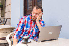 Young man with headache sitting in cafe with laptop and coffee. Royalty Free Stock Images
