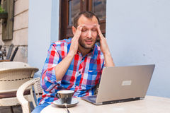 Young man with headache sitting in cafe with laptop and coffee. Royalty Free Stock Photography