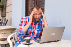 Young man with headache sitting in cafe with laptop and coffee. Stock Photo