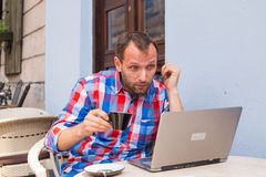 Young man with headache sitting in cafe with laptop and coffee. Stock Photography