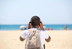 Young man with headphones and bag standing at the beach Royalty Free Stock Image