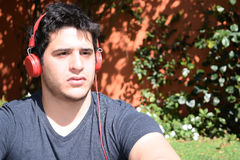 Young man with headphones in the garden Royalty Free Stock Photography