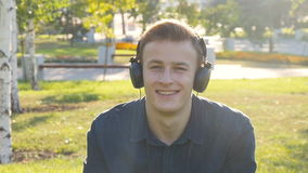 Young man with headphones at green grass stock video footage