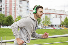 Young man with headphones jogging outdoors Stock Photo