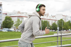 Young man with headphones jogging outdoors Royalty Free Stock Image