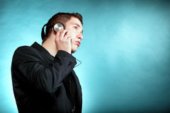 Young man with headphones listening to music. Young man student with headphones listening to music blue background Royalty Free Stock Photos
