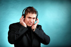 Young man with headphones listening to music. Young happy man student with headphones listening to music blue background Royalty Free Stock Photo