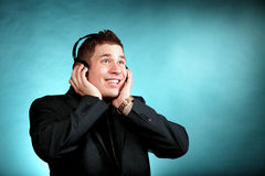 Young man with headphones listening to music. Young happy man student with headphones listening to music blue background Stock Photography