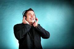 Young man with headphones listening to music. Young happy man student with headphones listening to music blue background Royalty Free Stock Images