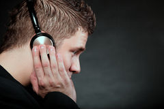 Young man with headphones listening to music. Profile of a man student with headphones listening to music black grunge background Stock Photos