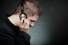 Young man with headphones listening to music. Profile of a man student with headphones listening to music black grunge background Royalty Free Stock Images