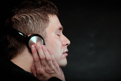Young man with headphones listening to music. Profile of a man student with headphones listening to music closed eyes black grunge background Royalty Free Stock Photos