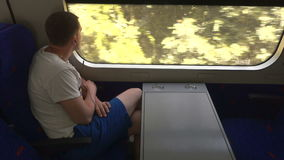 Young man in headphones looking out window train stock footage